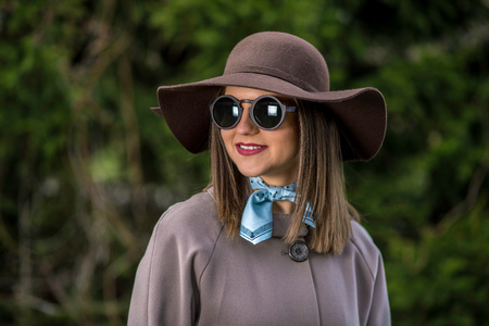 Young woman in hat, raincoat and sunglasses is posing in the park during a sunny spring day. Shallow depth of field. Stock Photo