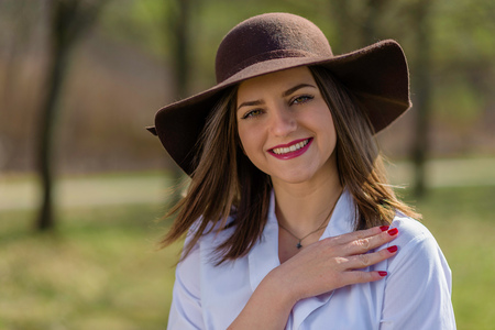 Portrait of a smiling young woman, holding her hand on her shoulder and wearing a hat in a park during spring. Woman bowed her head head to the left side of frame. Medium shot. Shallow depth of field.