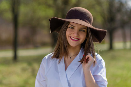 Portrait of a smiling young woman wearing a hat in a park during spring. Woman bowed her head head to the right side of frame. Medium shot. Shallow depth of field.