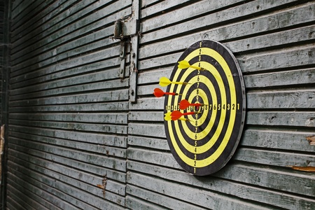 Dartboard on wood wall  Stock Photo - 10316666