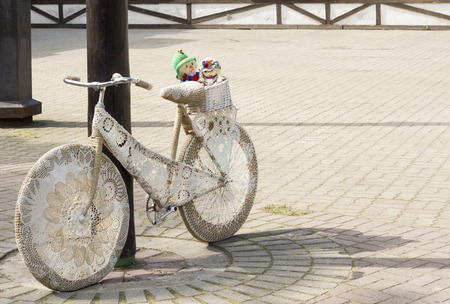 retro bike decorated with embroidery and soft doll in a basket.