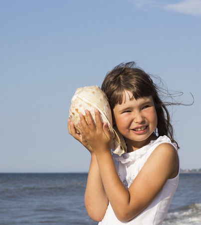 Summer vacation - beautiful girl with shell at the beach.
