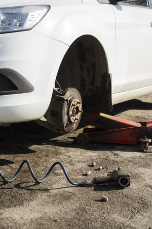 Car without wheel and lift up by hydraulic, waiting for tire replacement Banco de Imagens