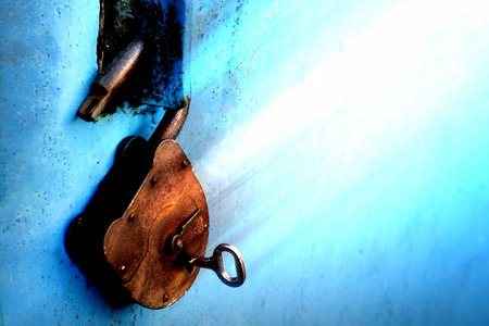 Old rusty lock with a key on a blue background