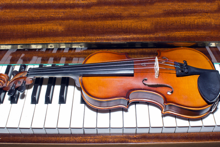 Very old violin lying on the piano.