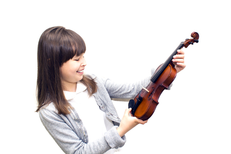 the child holds the violin and smiling.