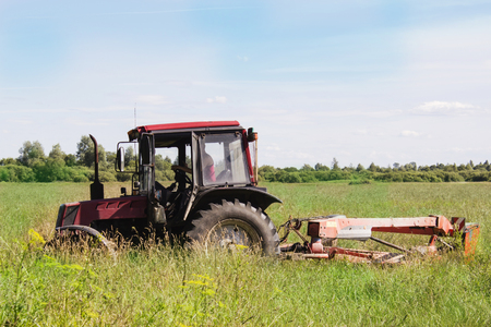 Old small tractor mows the grass