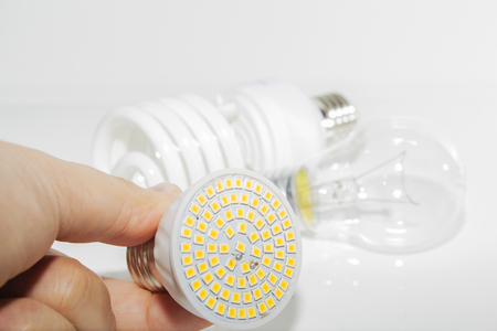Several different led bulbs and compact fluorescent lamps and the male hand on a light background.