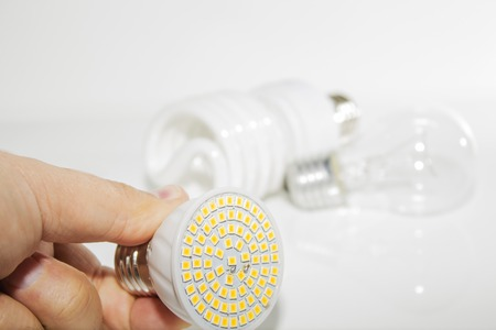 Several different led bulbs and compact fluorescent lamps and the male hand on a light background