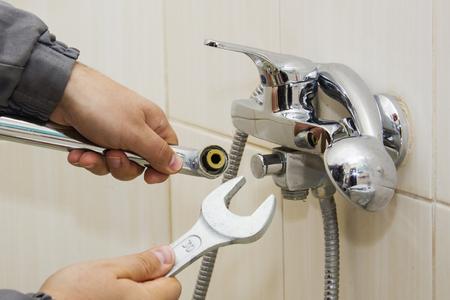 Ręce hydraulik mocujące zawór wody z kluczem
