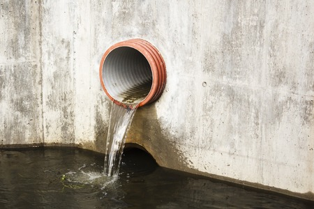 Toxic water running from sewers in dirty underground sewer for dredging drain tunnel cleaning.