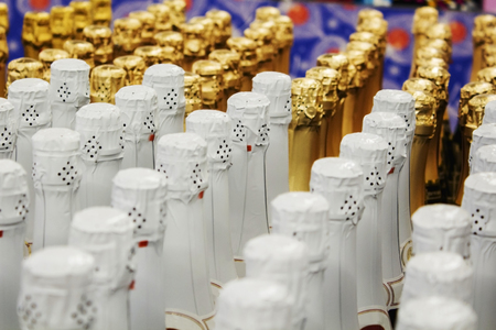 Big amount of golden and white champagne bottles necks and top caps at standing the light background Stock Photo