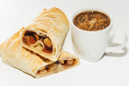 Apple strudel and a mug of coffee on the table. Stock Photo