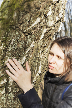 Girl hugging a huge tree trunk in the Park, smiling at the camera. The concept of protection of nature.