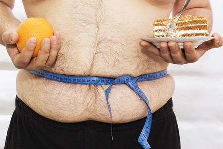 The fat man is tied with a measuring tape. Holds in the hands of cake and oranges. Diet. Difficult choice. Fitness. Sport.