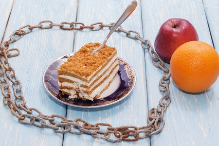 healthy eating concept, a piece of cake on a wooden table is surrounded by a metal chain. Next to an Apple and an Orange. Stock Photo