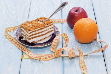 healthy food concept, piece of cake on wooden table and measuring tape. Next to an Apple and an Orange. Stock Photo