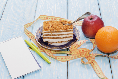 healthy food concept, piece of cake on wooden table and measuring tape with Notepad and pen. Next to an Apple and an Orange.