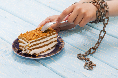 girl eating delicious cake on light blue background. Hands tied with chains. The concept of proper nutrition. Diet.