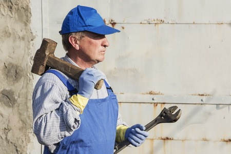 Wworker in blue overalls with a sledgehammer and a wrench. Serious look.