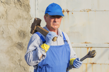 worker in blue overalls with a sledgehammer and a wrench. Serious look.