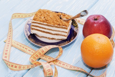 healthy food concept, piece of cake on wooden table and measuring tape. Stock Photo