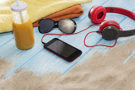 phone with headphones and sunglasses on a blue background, on a summer beach. Stok Fotoğraf