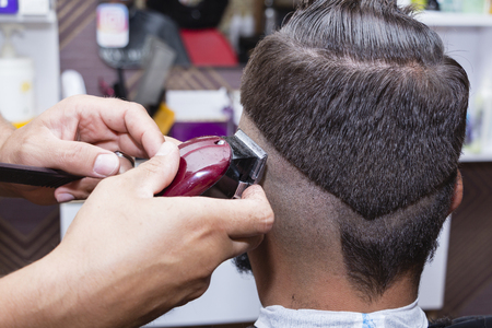 mens hair Styling and grooming with the help of scissors machine and hair clippers in the hair salon Stock Photo