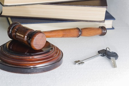 Judge hammer and house key on light background. The concept of property law. Estate sale