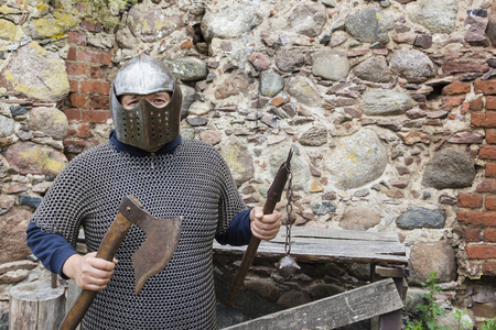 Medieval old knight helmet and chain mail for protection in battle. Very heavy headdress on stand in nature. Middle ages armor concept. Stock Photo