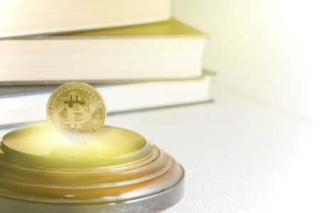 Single bitcoin coin or icon standing in sharp focus on a reflective surface with gold colored .