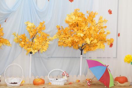 Orange pumpkins and dry autumn leaves. Bright umbrella. Bright stylish cozy interior home interior. Autumn decoration.