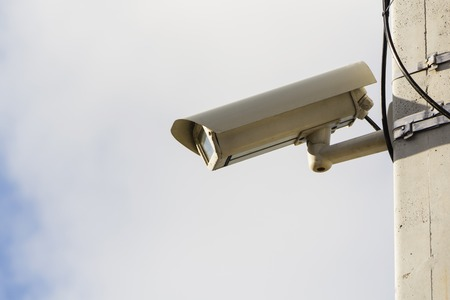 Modern compact video surveillance camera on support post in public areas on white background general plan.