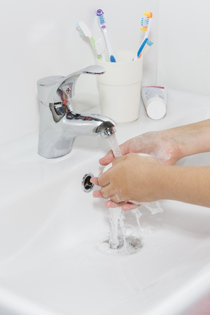 Hygiene concept. Washing hands with soap under the faucet with water. Stock Photo