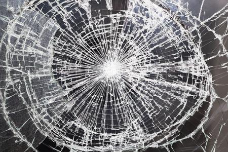 Broken windshield glass on a grayish background