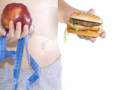 Burger cheeseburger in hands with measure tape isolated on white background. Healthy weight loss diet concept. Reklamní fotografie