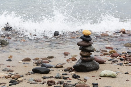 A pyramid of stones with a bright stone at the top stands on the sandy beach. The concept of leadership Imagens