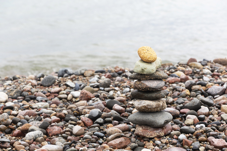 A pyramid of stones with a bright stone at the top stands on the sandy beach. The concept of leadership.