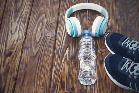 Sports equipment. Sneakers, water and headphones on wooden background.