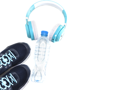 Sports equipment. Sneakers water and headphones, on a white background.