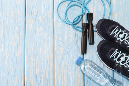 sneakers water bottle, and jump rope on light blue wooden background Stockfoto