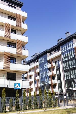 Modern apartment building in sunny day against blue sky.