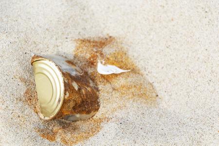 un vecchio barattolo di latta arrugginito lasciato da un uomo su una spiaggia sabbiosa