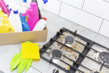 Cleaning a gas stove with kitchen utensils, household concepts, or hygiene and cleaning