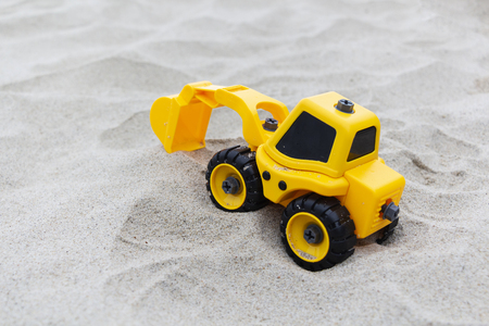 Yellow excavator toy in the sand, on the beach. toys for boys