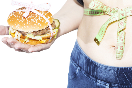 Burger cheeseburger in hands with measure tape isolated on white background. Healthy weight loss diet concept Stock Photo