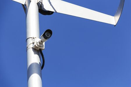 Twin security cameras on a pole against a blue sky
