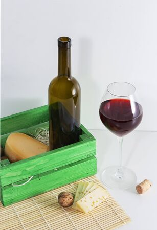 A bottle of red wine with a glass and a piece of cheese