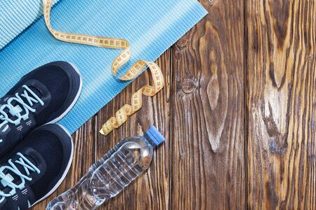 Healthy lifestyle and sports background. Sports shoes and water bottle on wooden background with copyspace, topview