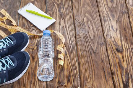 Healthy lifestyle and sports background. Sports shoes, Notepad and pen, and water bottle on wooden background with copyspace, topview